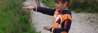 Foto: Ett barn med mobil och hörlurar pekar framåt